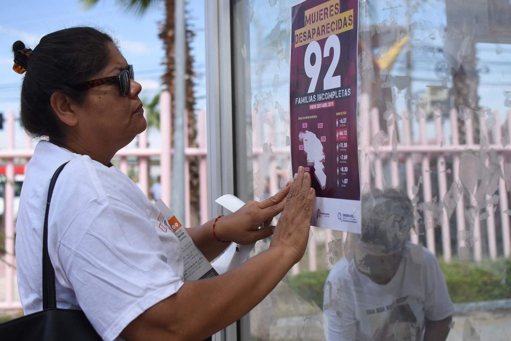 Una madre que busca a su hija desaparecida coloca en el Memorial del Campo Algodonero un cartel con datos de familias incompletas en Ciudad Juárez. Foto: Rey R. Jáuregui