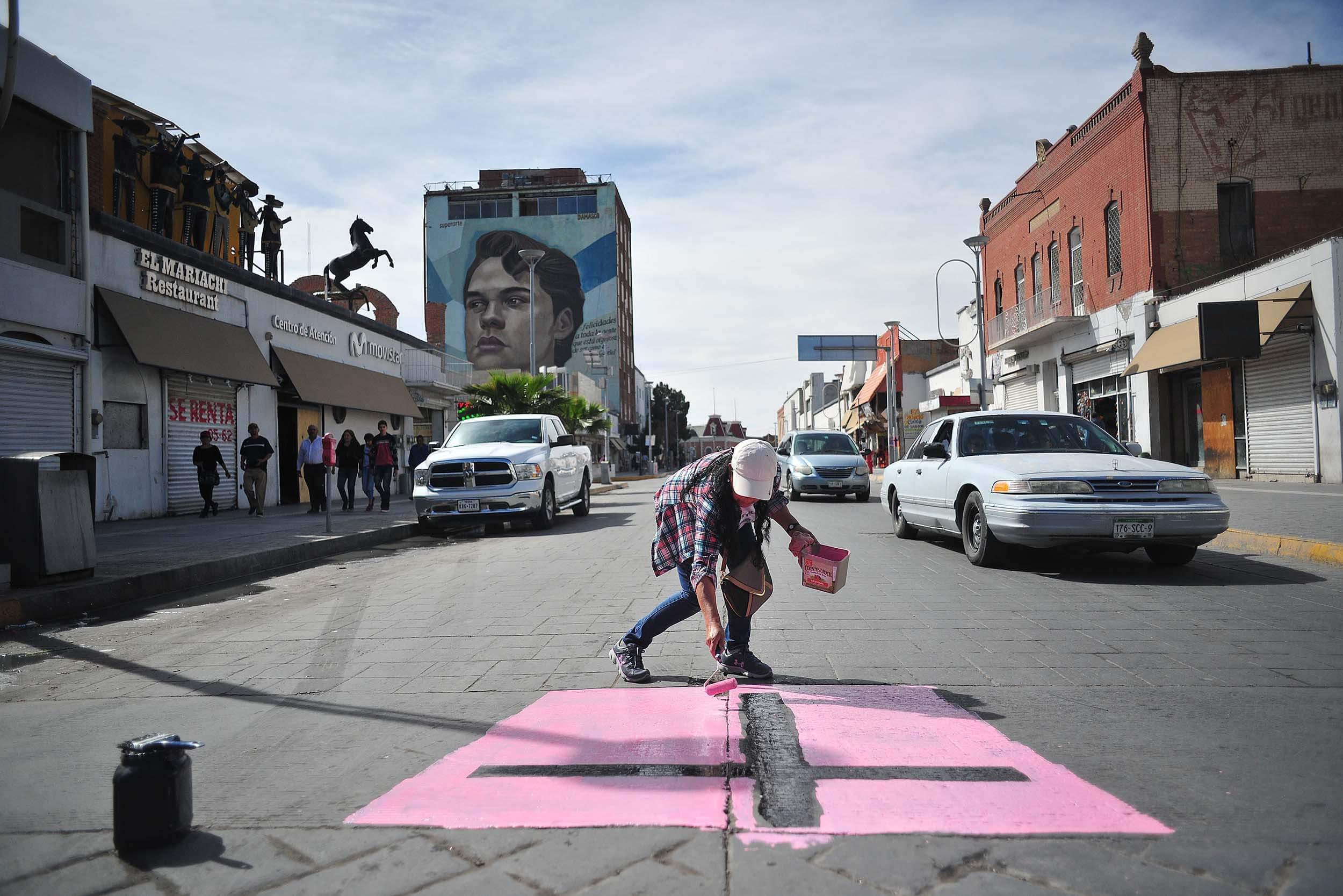 Una cruz negra sobre un cuadro rosa es pintada sobre la avenida Juárez, corredor turístico que une a Ciudad Juárez con El Paso, Tejas. En la zona dominan los bares, ahí operó por años el Noa Noa, un centro nocturno que inmortalizó el cantante Juan Gabriel. Foto: Rey R. Jáuregui